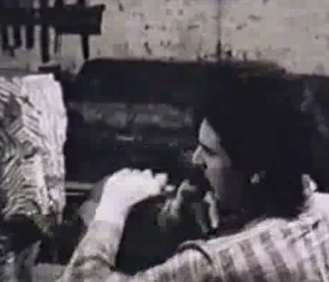 Film still of a man in a vertically striped shirt (Chaim Gross) with his back to the viewer, carving a sculpture depicted at left.