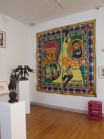 Photo of a white gallery wall with a large, colorful tapestry hung on it. To the left of us there are two small, dark sculptures mounted on rectangular white blocks. On the very bottom right of the frame there is a small red stool beneath the tapestry.