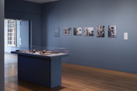 Photo of the encased wooden sculpture tools and equipment featured in the exhibit. On the far right faded navy wall are a series of black and white photos of Chaim Gross at work.