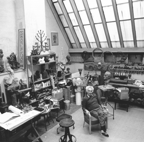 Black and white photo of Chaim Gross sitting in his studio surrounded by his art, his workbench, and his tools. The studio's large skylight looms above, at the top right corner of the photo.