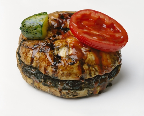 Photograph by Sharon Core of a hamburger covered in sauce with pickle and tomato on top of bun arranged to look like the sculpture by Oldenburg