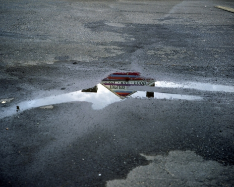 Topless bar reflected in puddle, Doylestown, Pennsylvania, 2010. Archival Pigment Print, Editions of 5. Available Sizes: 20 x 24 inches, 30 x 40 inches, and 40 x 50 inches