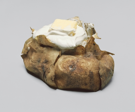 Oversized baked potato with sour cream and butter based on Claes Oldenburg sculpture. Presented as a photograph.