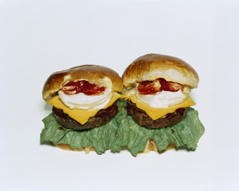 Photograph by Sharon Core. Two cheeseburgers with toppings arranged to look like the sculpture by Claes Oldenburg.
