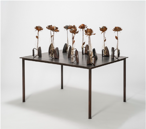 Karin Broker  First Wives, 2018  11 antique irons, wired metal roses with crystals on steel table  44.5 x 48 x 36 inches  Inquire