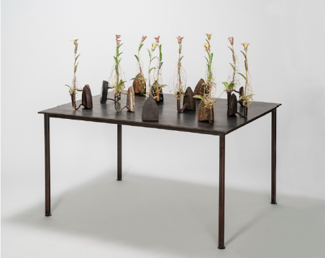 Karin Broker  Second Wives, 2018  11 antique irons, wired metal flowers with crystals on steel table  44.5 x 48 x 36 inches  Inquire