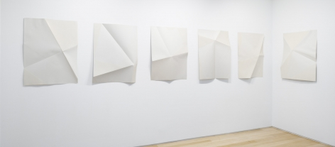 six prints which have been folded in various ways displayed on a wall