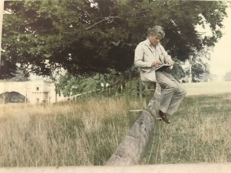 man sitting on a fence drawing