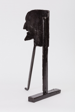 bronze statuette of a man's face on two long supports