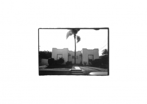 picture of the outside of a house with a palm tree