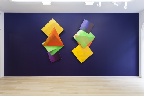 two triangular shaped canvases on an indigo wall