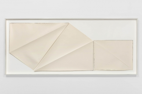multiple pieces of paper that have been folded and cut put into a frame on a white boad