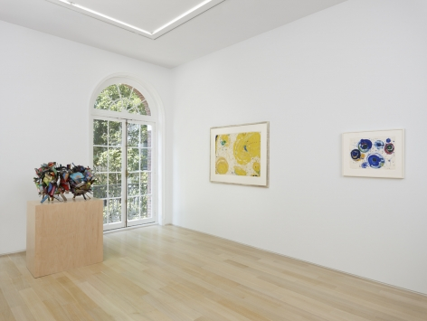 installation view of two framed works on paper with a sculpture in the foreground