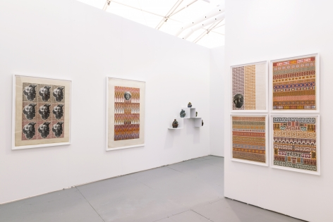 Installation view of an art fair booth. Sculptures and collages are on the walls