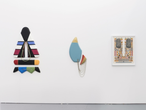 Installation view of an art fair booth. Sculptures and a collage are on the walls