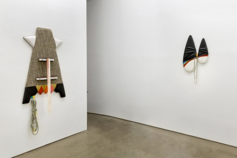 "Installation view of Trish Tillman's exhibition ""Stage Diver"", which shows plush sculptures on the walls by a doorway"
