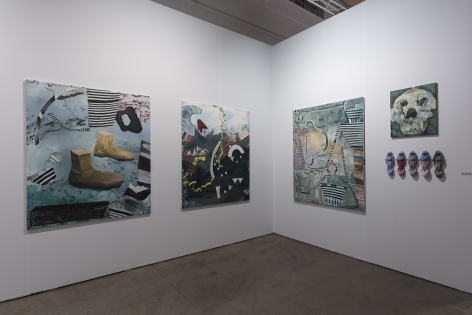 Installation view of an open art fair booth, showcasing artwork on the walls.