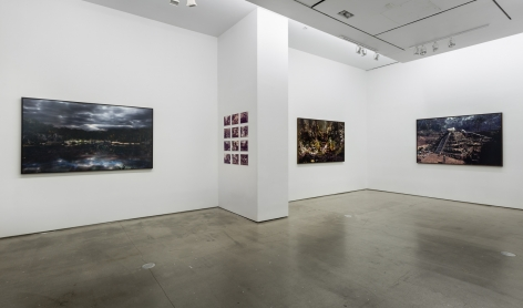 "An installation view of Jasper de Beijer's exhibition, ""The Brazilian Suitcase"". Framed photographs are on the walls. Small pieces are arranged in a grid."