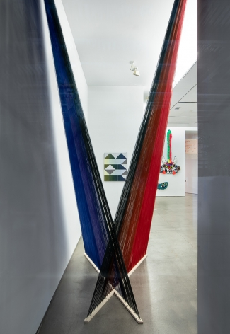 """Installation view of """"Adriadne Unraveling"""". Textile works are hung on the wall. An installation hangs in an """"X"""" in the foreground."""