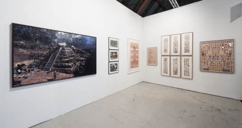 Installation view of an art fair booth, showcasing paintings, collages, and photos on the walls.