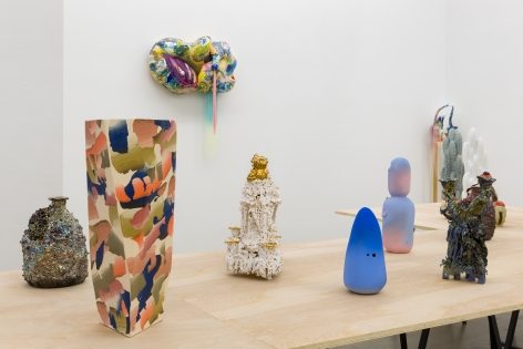 """An installation view of the group exhibition """"Morph"""". There are many sculptures on a table in the gallery"""