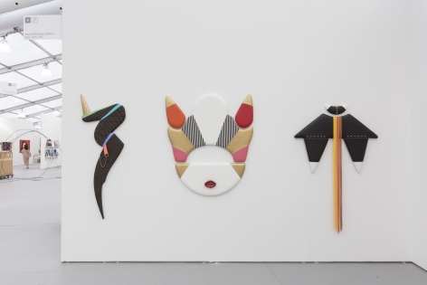 Installation view of an art fair booth, showcasing flat sculptures on the walls