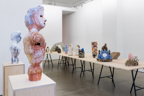 """An installation view of the group exhibition """"Morph"""". There are many sculptures on a table in the gallery. Busts are on pedestals"""