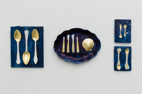 An installation view of artwork by Julie Schenkelberg. Mixed media pieces silverware casts line the walls