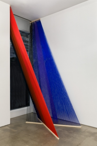 An installation view of a large string installation, hung next to a window.