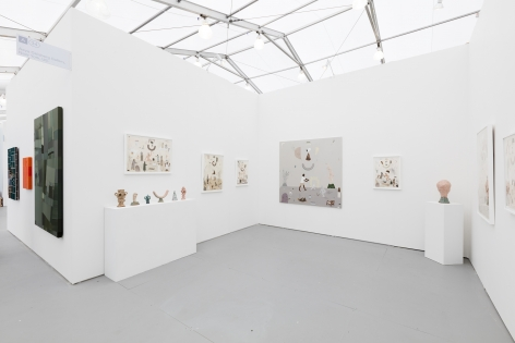 Installation image of the art fair booth at UNTITLED Miami. Framed works are on the walls and ceramic sculptures are on podiums
