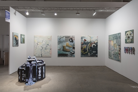 """Installation view of an open art fair booth, showcasing artwork on the walls. A large """"wishing well"""" installation is on the floor."""