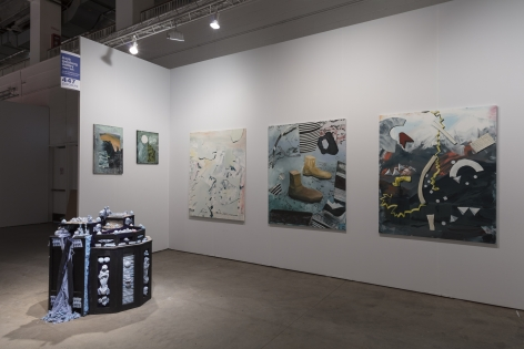 "Installation view of an open art fair booth, showcasing artwork on the walls. A large ""wishing well"" installation is on the floor."