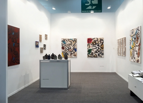 Installation view of the art fair booth at Zona Maco. Paintings are on the walls and sculptures are on a table