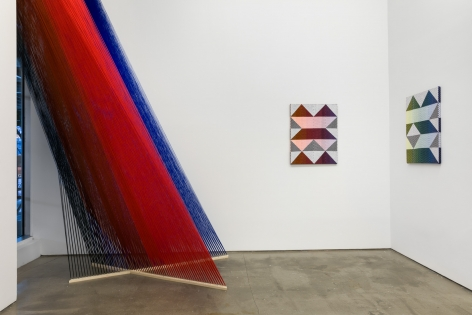"Installation view of ""Adriadne Unraveling"". Textile works are hung on the wall. A large string installation in the left corner"
