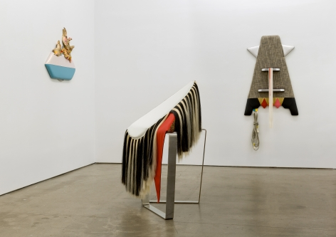 "Installation view of Trish Tillman's exhibition ""Stage Diver"", which shows plush sculptures on the walls and standing on the floor."