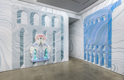 Installation view from Lauren Clay's solo exhibition. A large sculptural piece hangs on the wall. The wall is papered with custom-made wallpaper.