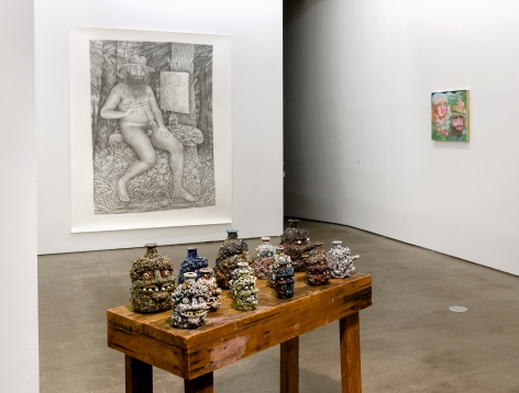 Rebecca Morgan's face jugs on a table with a large drawing