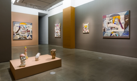 An installation view of paintings and sculptures by Gudmundur Thoroddsen. Large and medium paintings are hung on the wall by ceramic sculptures on pedestals.