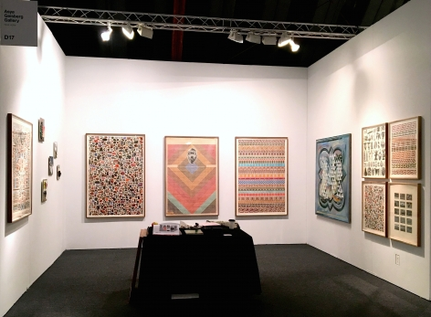 Installation view of the booth at Art Los Angeles Contemporary. Large works are on the wall and a table with sculptures is in the middle of the booth