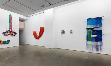 """Installation view of """"Adriadne Unraveling"""". Textile works are hung on the wall."""