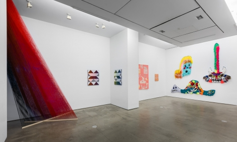 """Installation view of """"Adriadne Unraveling"""". Large sculptural installation in left corner, with textile works on the wall."""