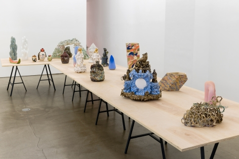 "An installation view of the group exhibition ""Morph"". There are many sculptures on a table in the gallery"