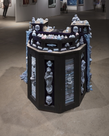 """Installation view of an open art fair booth, showcasing a large """"wishing well"""" installation on the floor."""