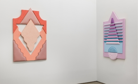 Installation views of Leah Guadagnoli's solo exhibition. Geometric sculptures made from fabric, foam, and pumice stone line the walls next to a corner.