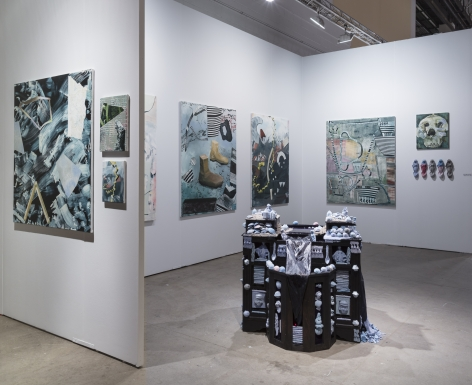 """Installation view of an open art fair booth, showcasing artwork on the walls. A large """"wishing well"""" installation is in the middle of the floor."""