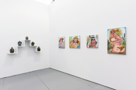Installation view of an art fair booth. Sculptures and paintings are on the walls