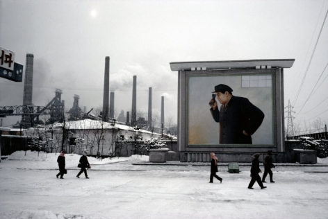 Hiroji Kubota, At the Kim Chaek Ironworks; the billboard shows Kim Il-sung peering into a furnace, Chongjin, North Korea, 1986, dye-transfer print, 20 x 24 inches/50.8 x 61 cm © Hiroji Kubota/Magnum Photos