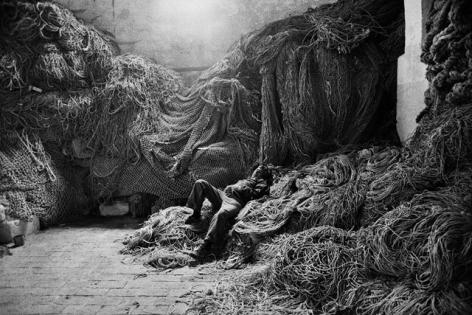 Sebastião Salgado, A tuna fisherman asleep on a net, Trapani, Sicily, Italy, 1991, gelatin silver print, 24 x 35 inches/61 x 89 cm