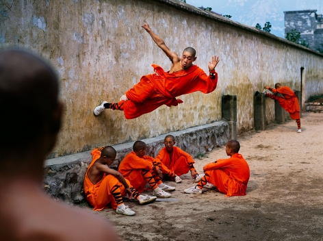 A young monk runs along the wall over his peers at the Shaolin Monastery in Henan Province, China, 2004, ultrachrome print, 40 x 60 inches/101.6 x 152.4 cm