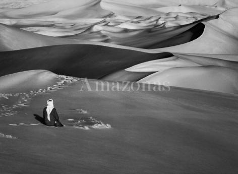 Sebastião Salgado. Man praying in the sand dunes in Maor, Tadrart. South of Djanet, Algeria. 2009. Gelatin silver print. 180 x 125 cm. © Sebastião Salgado/Amazonas Images